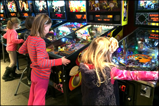 Girls Playing Pinball at Birthday Party